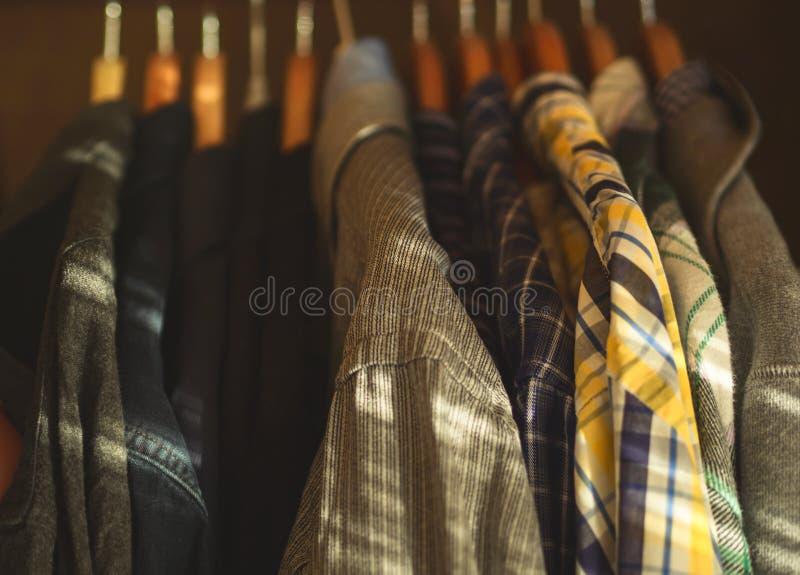 Man`s closet hangers shirts closeup. Man`s closet. Hangers with shirts closeup. Male wardrobe stock image