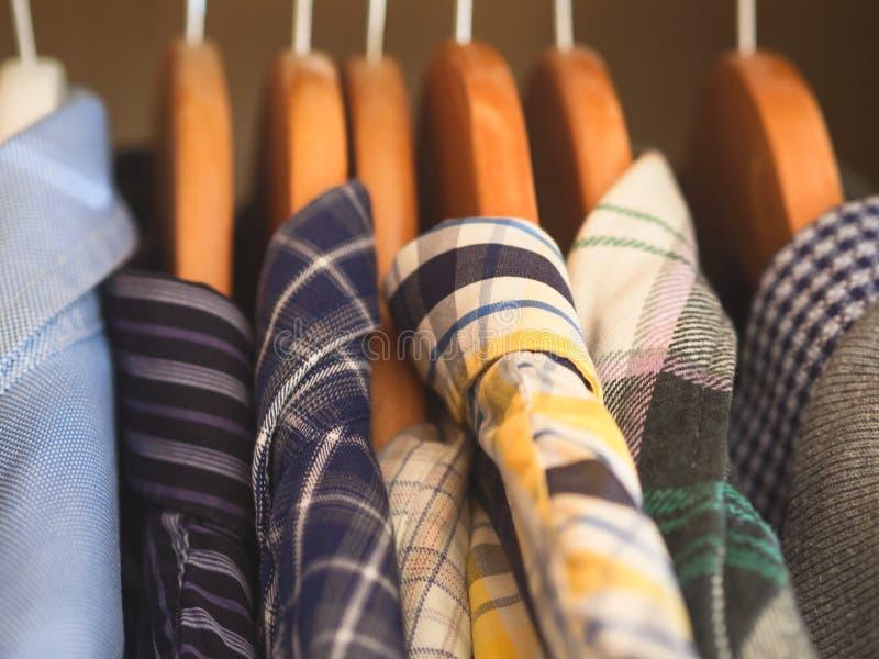 Man`s closet hangers shirts closeup. Man`s closet. Hangers with shirts closeup. Male wardrobe stock photography