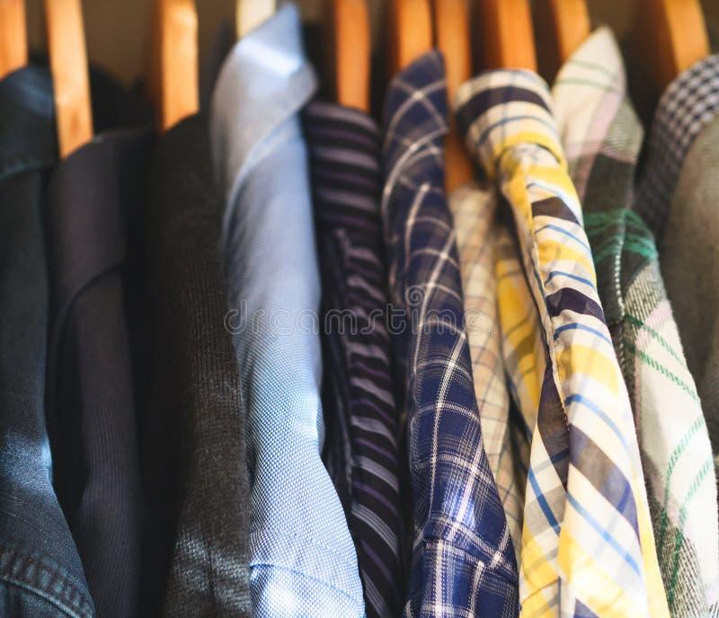 Man`s closet hangers shirts closeup. Man`s closet. Hangers with shirts closeup. Male wardrobe stock photos