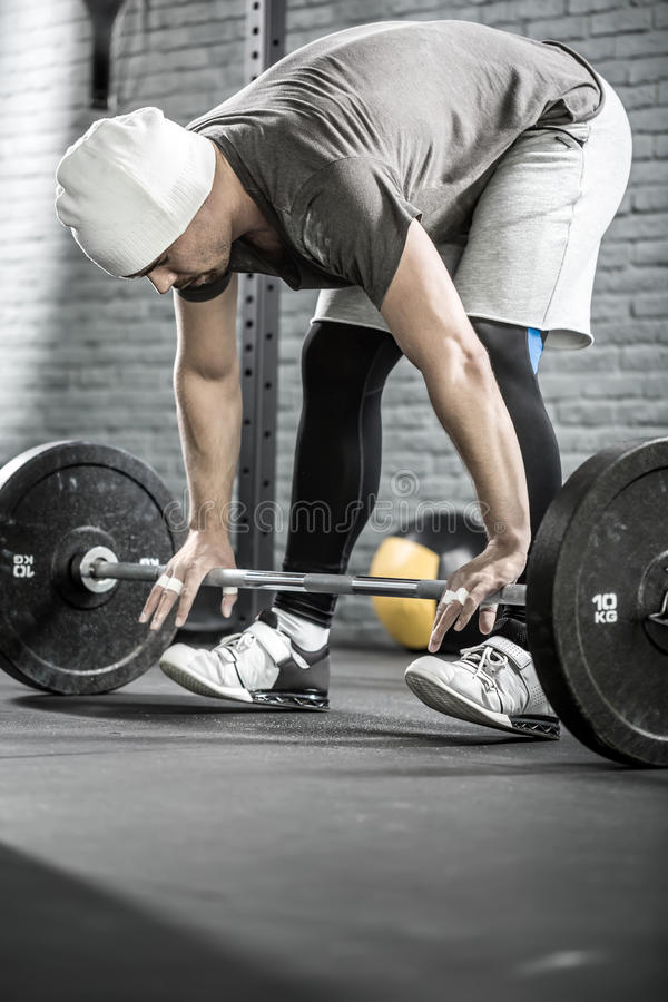 Man's crossfit workout with barbell. Amazing guy with a beard prepares to raise up a barbell in the gym on the gray brick wall background. He wears sportswear stock image