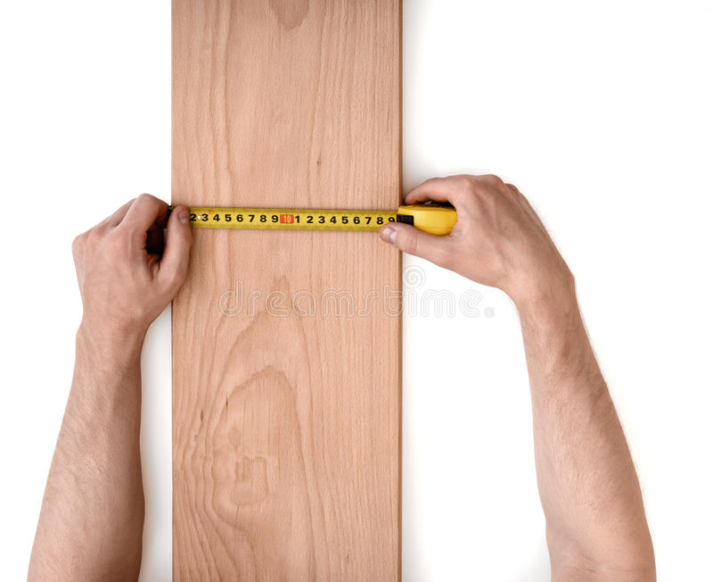 Man& x27; s da el tablón de madera de medición con una línea de la cinta aislada en el fondo blanco imagen de archivo