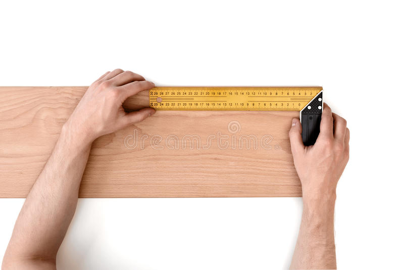 Man& x27; s da el tablón de madera de medición con una regla del hierro, aislada en el fondo blanco imagen de archivo libre de regalías