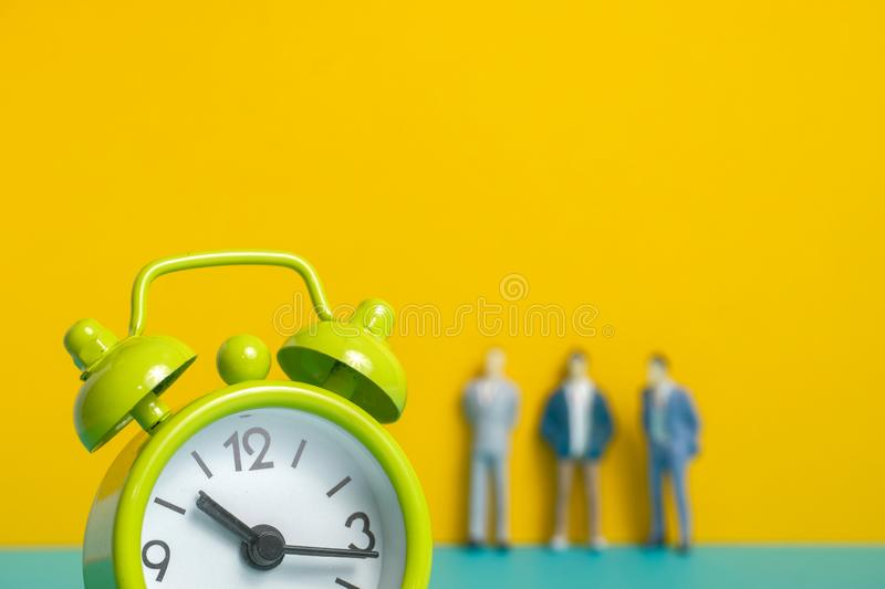 Man`s dummy next to a green vintage clock on a yellow background. stock photography