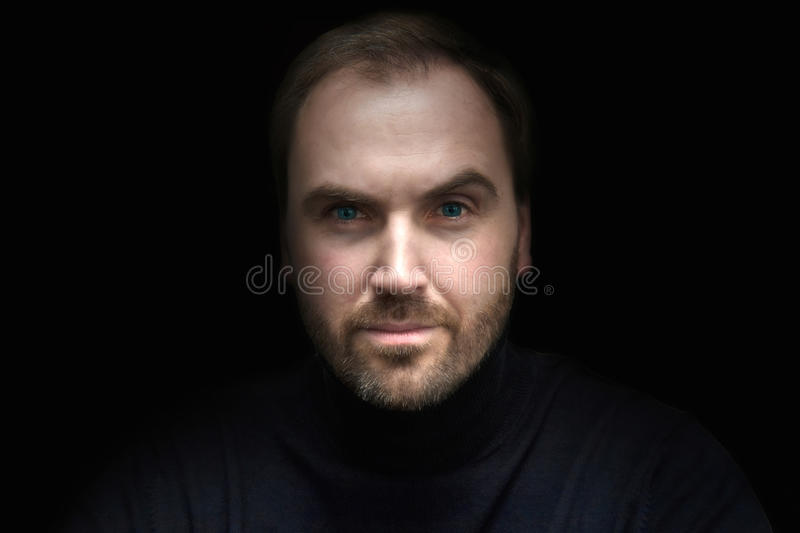 Man`s face. Close up portrait of a good looking man with beard and bright blue eyes royalty free stock image