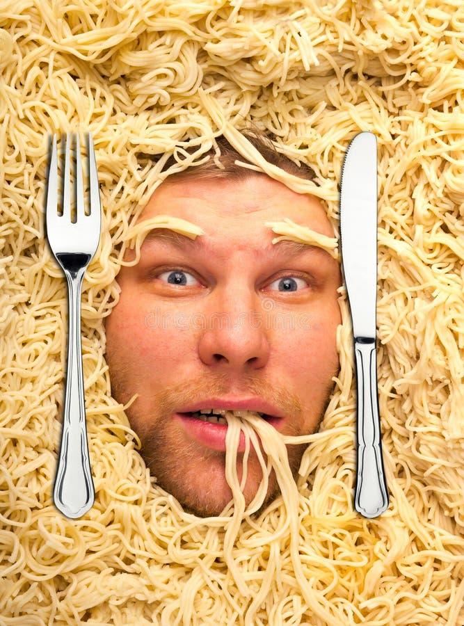 Man's face in pasta, closeup stock images