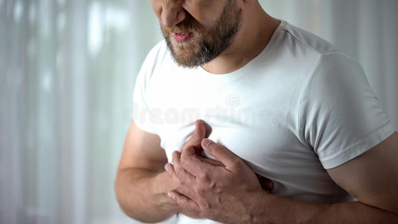 Man in 40s feeling strong chest pain, heart attack caused by stress, cardiology stock photo