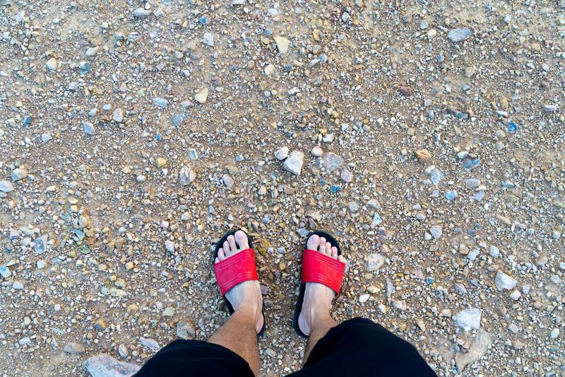 Man`s feet with red sandals. On gravel and brown soil royalty free stock photo