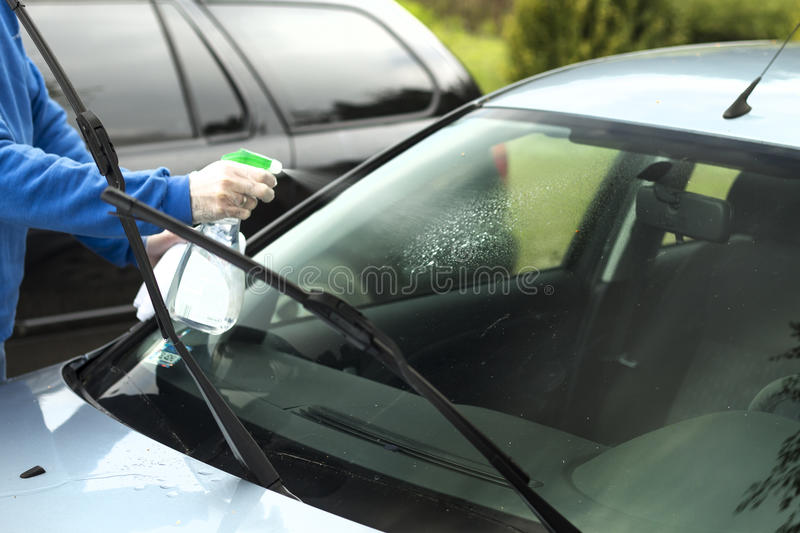 Man`s hand applies liquid to clean the windshield of the car window. stock photos
