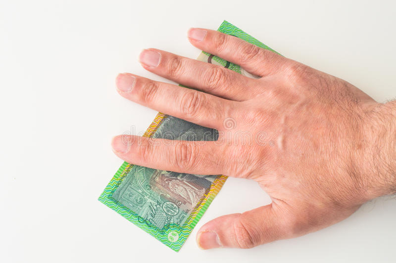 Man's hand on Australian Dollar. Banknote royalty free stock images