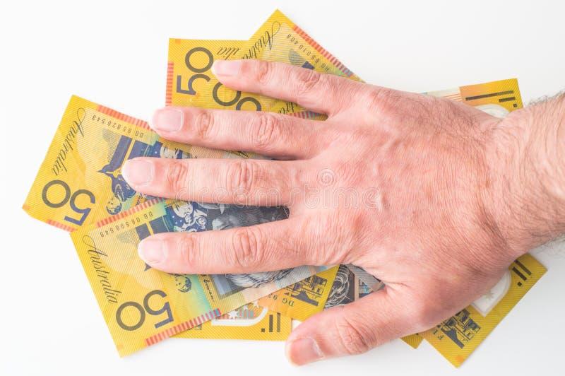 Man's hand on Australian Dollar. Banknote stock photography
