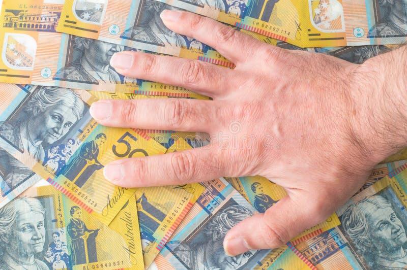 Man's hand on Australian Dollar. Banknote royalty free stock photo