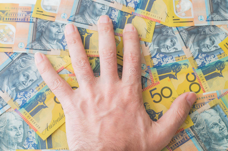 Man's hand on Australian Dollar. Banknote stock photo