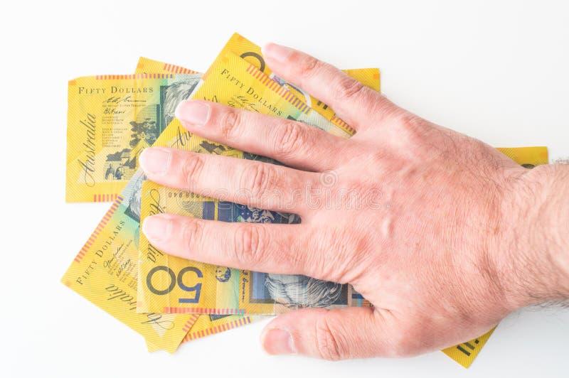 Man's hand on Australian Dollar. Banknote royalty free stock image