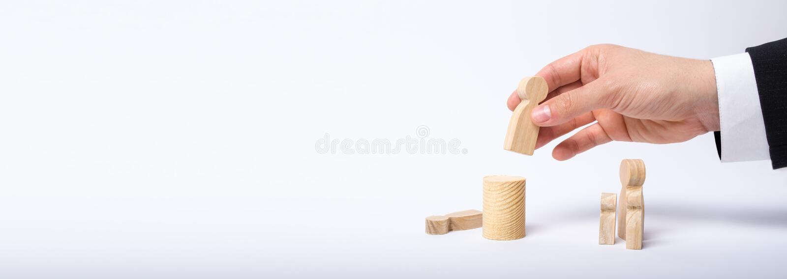 The man`s hand of a businessman in a business suit holds a wooden figure of a man in his hand and moves another figure from. His post. The concept of firing an stock photography