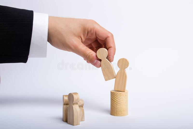 The man`s hand of a businessman in a business suit holds a wooden figure of a man in his hand and moves another figure. From his post. The concept of firing an stock photo