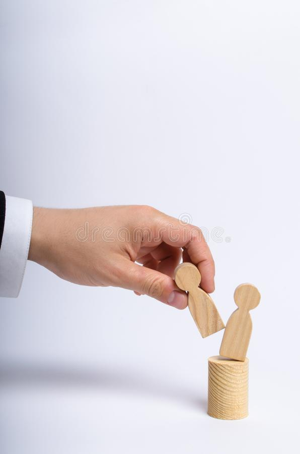 The man`s hand of a businessman in a business suit holds a wooden figure of a man in his hand and moves another figure. From his post. The concept of firing an royalty free stock images