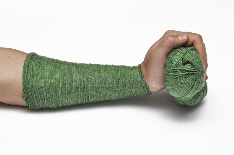 Man& x27; s hand en groen garen op een witte achtergrond crochet De ruimte van het exemplaar royalty-vrije stock foto