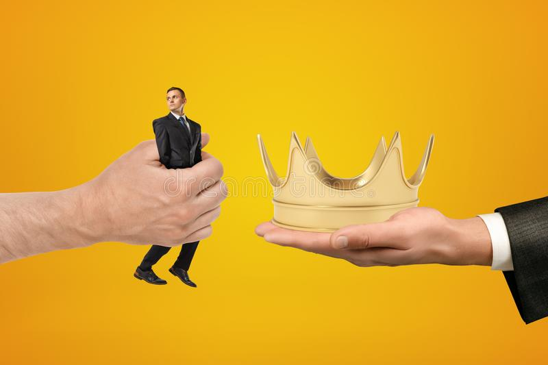 Man`s hand exchanging tiny businessman for gold crown held in another man`s hand on amber background. royalty free stock image