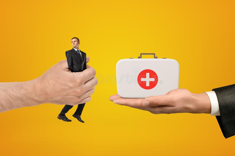 Man`s hand exchanging tiny businessman for medical bag held in another man`s hand on amber background. Medical supplies. Medical business. Health assessment royalty free stock photos