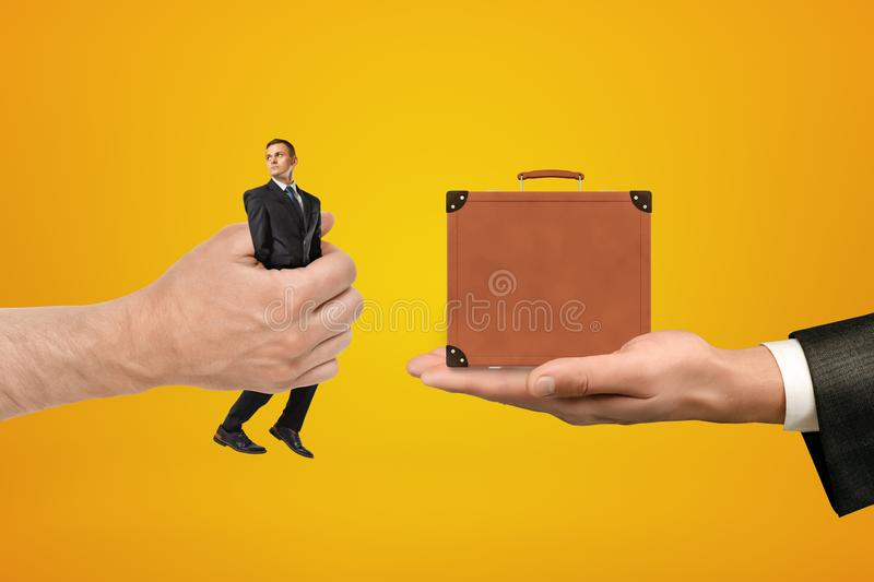 Man`s hand exchanging tiny businessman for tiny brown travel case held in another man`s hand on amber background. stock images