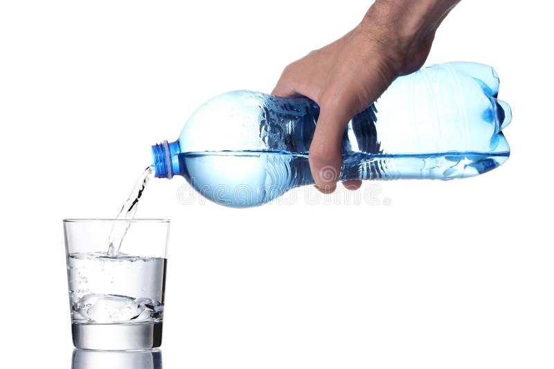 Man`s hand fill a water glass with a plastic bottle, clipping path included stock photo