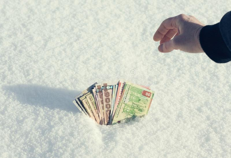 A man`s hand is getting money of south-east Asia from the snow in winter royalty free stock images