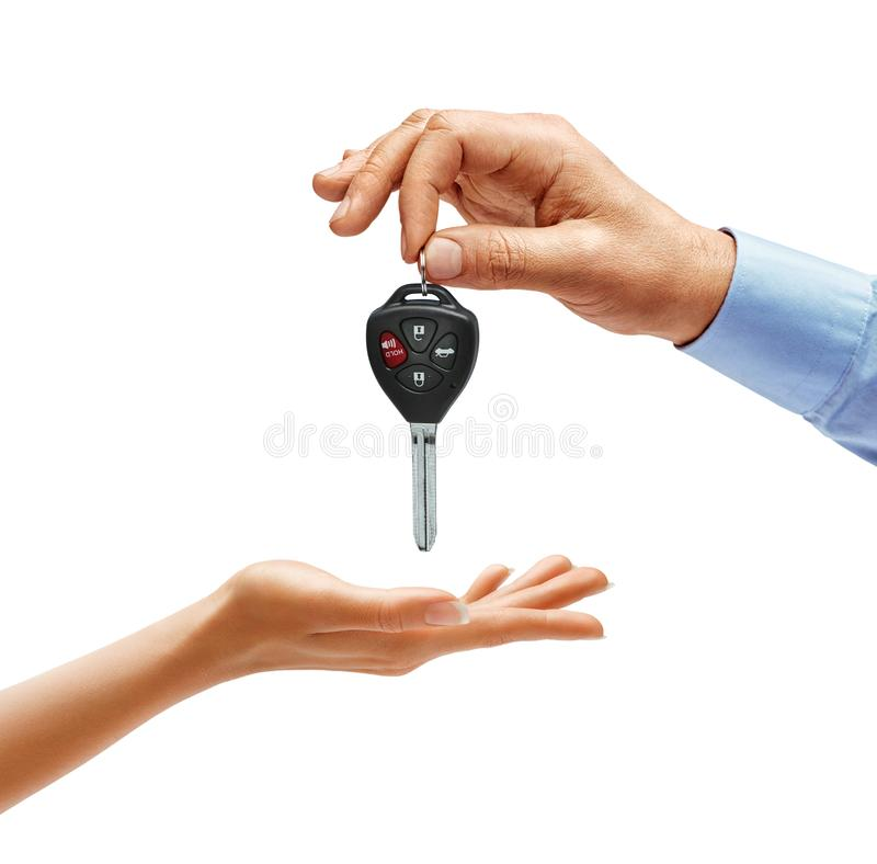 Man`s hand giving the car key to woman`s hand isolated on white background. royalty free stock images