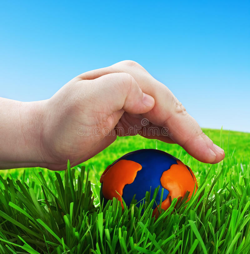 Man's hand on a globe made of plasticine royalty free stock image