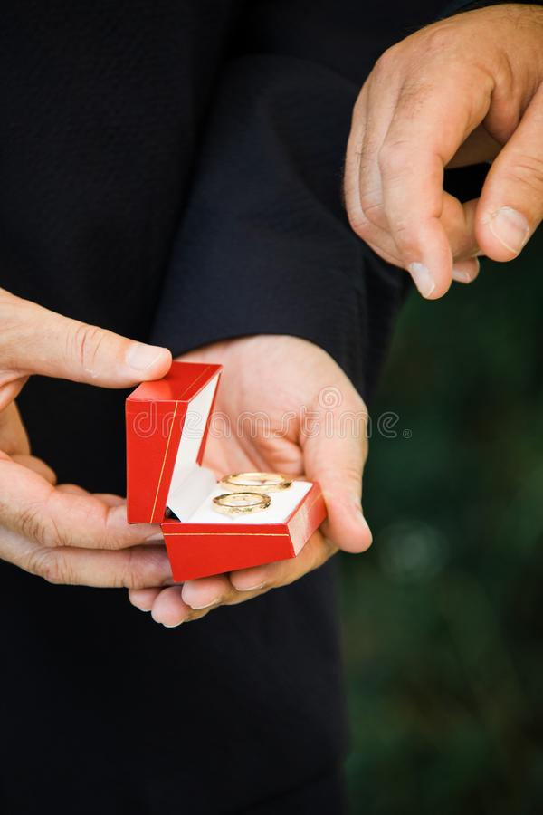 Man`s hand going to take wedding ring from red box stock photos