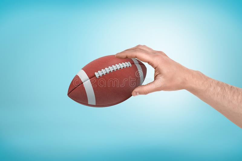 Man`s hand holding ball for American football on light blue gradient background. royalty free stock photos