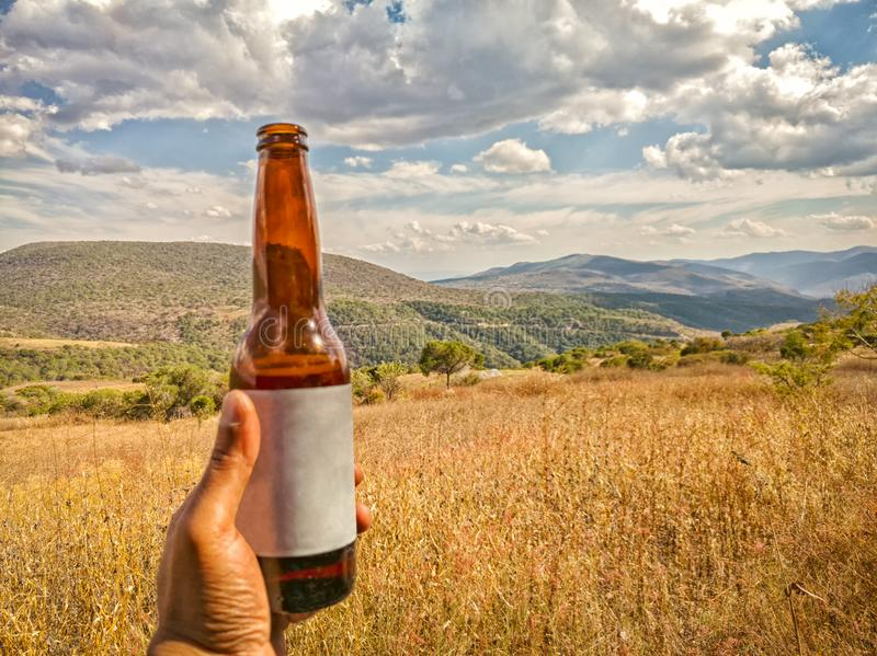 Hand holding a glass beer beverage outdoors, Sierra Madre del Sur mountains in the background. Travel in Mexico. A man`s hand is holding a beer beverage glass stock image