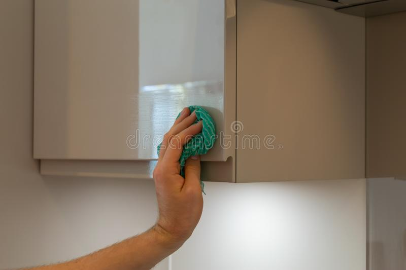 Man& x27;s hand holding a blue cleaning rag and cleaning furniture in the house. Kitchen, home, hygiene, domestic, housework, interior, chores, cleaner, dirty stock image