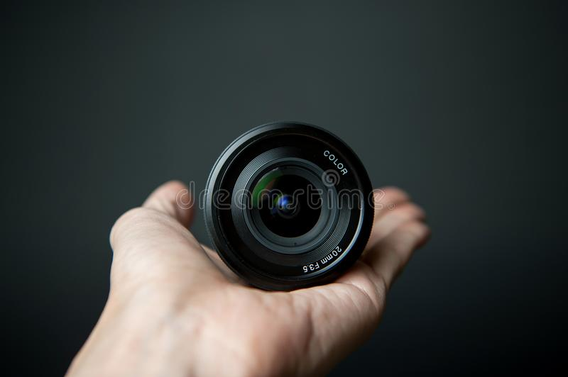 Man`s hand holding a camera lens on a black background. Man`s hand holding a camera lens on a black background stock image