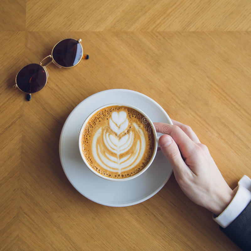 Man`s hand holding a cup of coffee royalty free stock photo