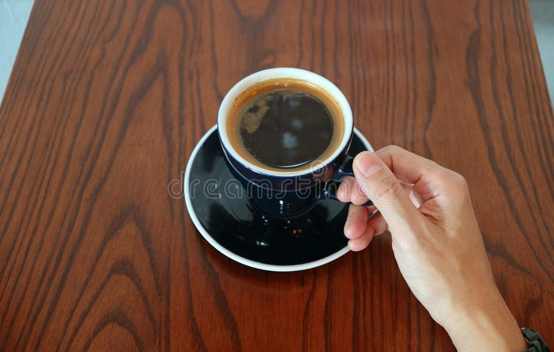 Man`s Hand Holding the Cup of Hot Black Coffee Served on Wooden Table royalty free stock image