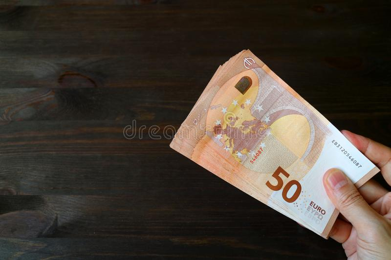 Man`s Hand Holding 50 EURO Banknotes on Dark Brown Wooden Background stock photos
