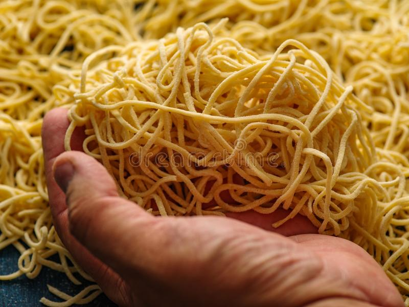 Man`s hand holding fresh homemade pasta. royalty free stock image