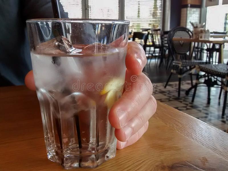 Man`s hand holding glass with water, ice cubes, lemon and straw stock image