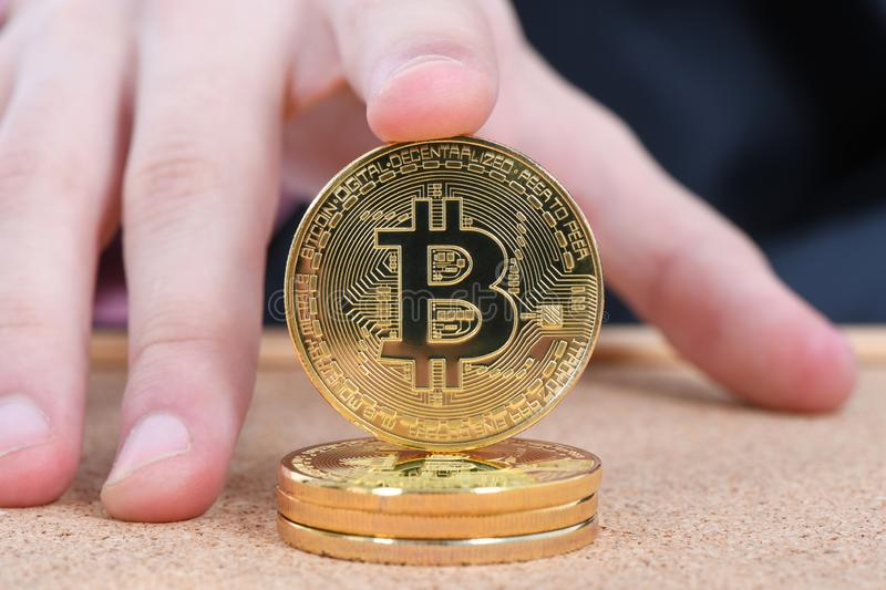 Man`s hand holding golden Bitcoin on brown textured cork background royalty free stock images