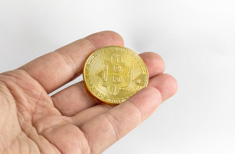 Man`s hand holding golden Bitcoin on white background royalty free stock photos