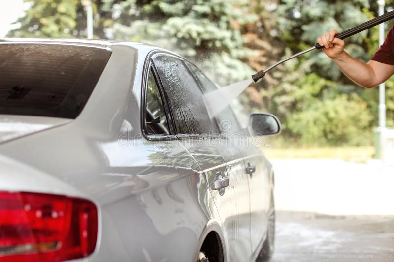 Man`s hand holding hose, spraying water to widow of silver car in self serve carwash, sun lit blurred green trees in background royalty free stock photography