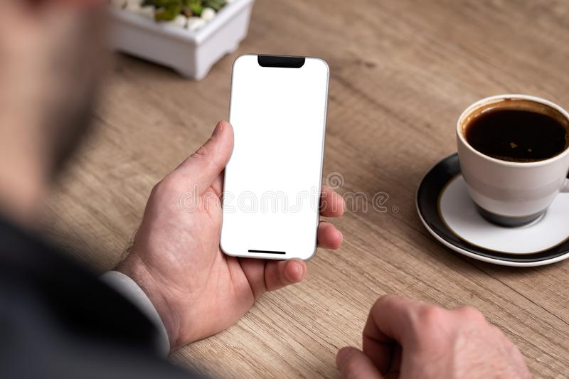 Man`s hand holding mobile phone on desk in office stock photo