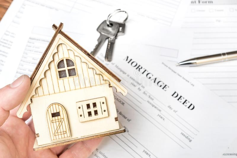 Man`s hand holding model of house over mortgage deed. Real estate concept stock images