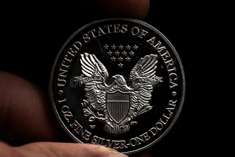 Man's hand holding a silver American coin, close-up of a quarter dollar coin isolated over black. Bag, dollars. Man's hand holding a silver American coin, which stock images