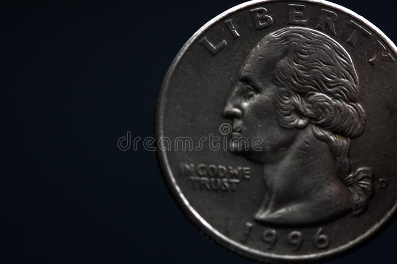 Man's hand holding a silver American coin, close-up of a quarter dollar coin isolated over black. Bag, dollars. Man's hand holding a silver American coin, which stock image