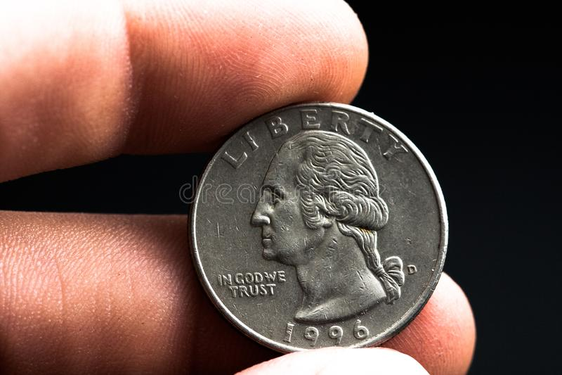 Man's hand holding a silver American coin, close-up of a quarter dollar coin isolated over black. Bag, dollars. Man's hand holding a silver American coin, which royalty free stock photo