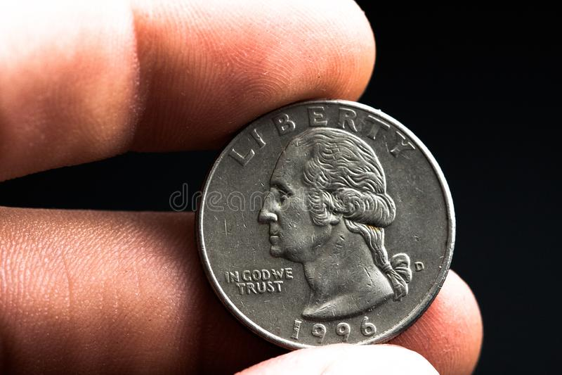 Man's hand holding a silver American coin, close-up of a quarter dollar coin isolated over black. Bag, dollars. Man's hand holding a silver American coin, which royalty free stock photos