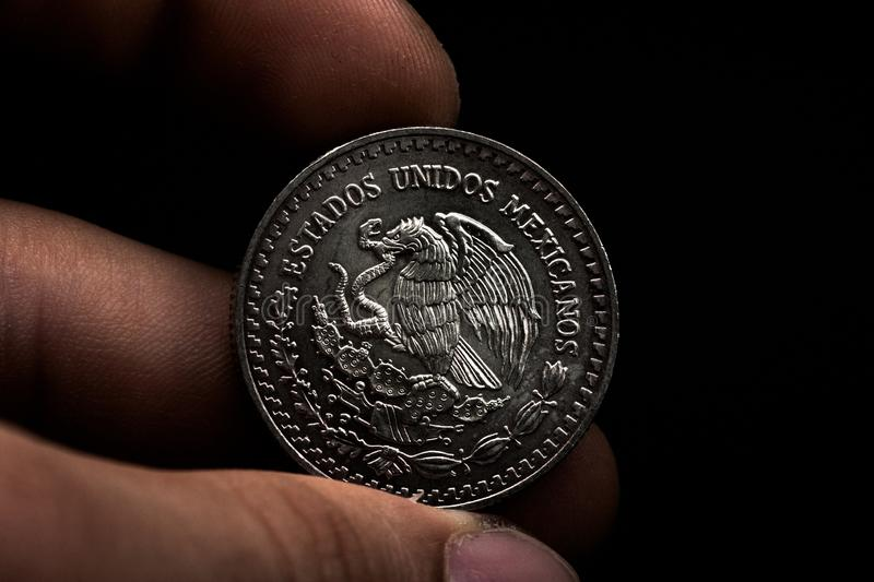 Man's hand holding a silver American coin, close-up of a quarter dollar coin isolated over black. Bag, dollars. Man's hand holding a silver American coin, which royalty free stock photography