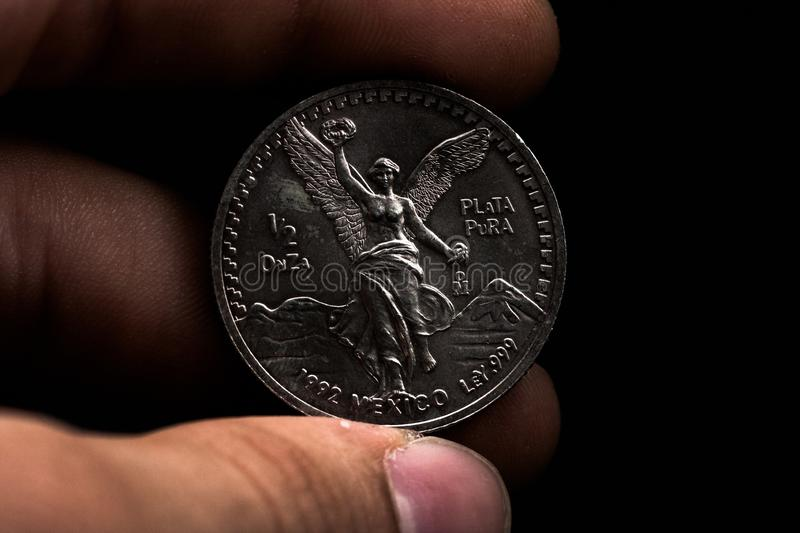 Man's hand holding a silver American coin, close-up of a quarter dollar coin isolated over black. Bag, dollars. Man's hand holding a silver American coin, which royalty free stock image
