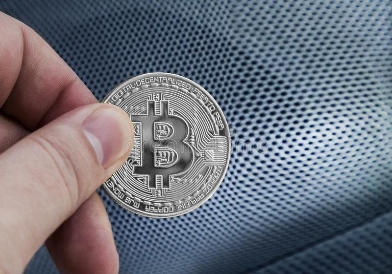 Man`s hand holding silver Bitcoin stock image